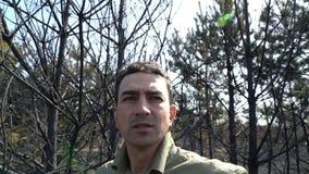Uomo nella disperazione che sta nell'incendio violento bruciato di af della foresta, disastro ecologico di catastrofe stock footage