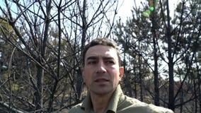 Uomo nella disperazione che sta nell'incendio violento bruciato di af della foresta, disastro ecologico di catastrofe video d archivio