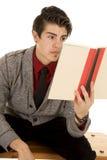 Uomo nella lettura del libro della tenuta del maglione Fotografia Stock