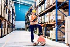 Uomo nella lista di controllo industriale del magazzino Fotografia Stock