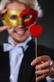Uomo nella maschera di carnevale con il simbolo di amore del bastone del cuore Fotografia Stock