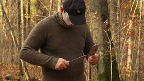 Uomo nella maschera di Halloween che affila i coltelli stock footage
