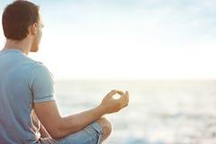 Uomo nella meditazione vicino al mare immagini stock