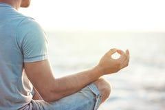 Uomo nella meditazione vicino al mare immagine stock