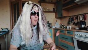 Uomo nella parrucca del ` s della donna in occhiali da sole che masticano alla tavola in cucina parody divertente video d archivio