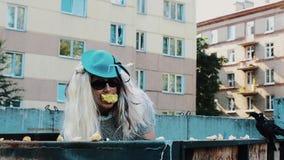 Uomo nella parrucca in occhiali da sole, cappello blu della donna in bidone della spazzatura con la mela in bocca parody video d archivio
