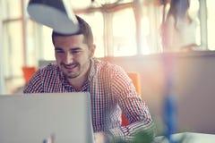 Uomo nella partenza moderna dell'ufficio che lavora al computer portatile immagine stock libera da diritti