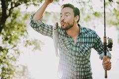Uomo nella pesca a quadretti della camicia sul fiume di estate immagine stock libera da diritti