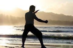 Uomo nella posizione di lotta sulla spiaggia fotografia stock