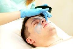 Uomo nella procedura del cosmetico della maschera Immagini Stock