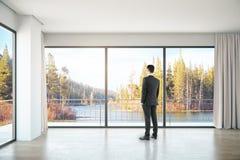 Uomo nella sala con la vista del paesaggio fotografie stock libere da diritti