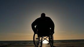 Uomo nella siluetta della sedia a rotelle vicino all'orizzonte di mare stock footage