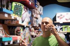 Uomo nelle chiamate del deposito alla moglie fotografie stock libere da diritti