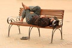 Uomo nepalese che dorme su un banco a Kathmandu, Nepal il 6 aprile, Fotografie Stock