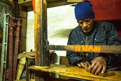Uomo nepalese che lavora nella sua officina di legno Immagine Stock