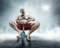 Uomo nerd che guida una piccola bicicletta Fotografie Stock Libere da Diritti