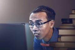 Uomo nerd che studia con il computer portatile Fotografie Stock