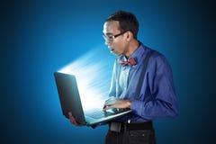 Uomo nerd con la posizione diritta di uso del computer portatile Fotografia Stock