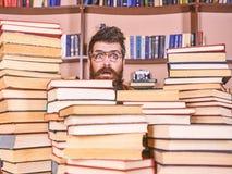 Uomo, nerd sul fronte sorpreso fra i mucchi dei libri in biblioteca, scaffali per libri su fondo Insegnante o studente con la bar immagini stock libere da diritti