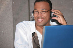 Uomo nero di affari che ascolta la musica sul suo computer portatile Fotografia Stock Libera da Diritti