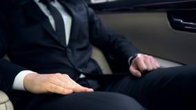 Uomo nervoso in vestito che si siede sul sedile posteriore dell'automobile, recente per la riunione importante fotografie stock