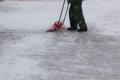 Uomo in neve di pulizia uniforme con una pala fotografie stock