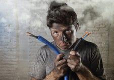 Uomo non addestrato che unisce cavo elettrico che subisce infortunio elettrico con il fronte bruciato sporco nell'espressione div Fotografie Stock