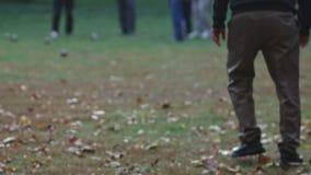Uomo non identificabile anziano che gioca boccia ad un parco in autunno archivi video