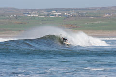 Uomo non identificato che pratica il surfing le onde Fotografie Stock Libere da Diritti