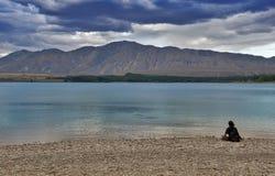 Uomo non identificato che si siede e che esamina lago Tekapo, isola del sud della Nuova Zelanda Immagine Stock Libera da Diritti