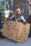 Uomo non identificato con il segno che chiede i soldi di comprare erbaccia su Broadway durante la settimana di Super Bowl XLVIII i Fotografia Stock