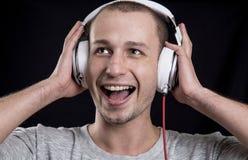 Uomo non rasato che ascolta la musica sulle cuffie Fotografie Stock Libere da Diritti