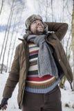 Uomo non rasato felice in un cappuccio della pelliccia nell'inverno nel looki di legni Fotografia Stock Libera da Diritti