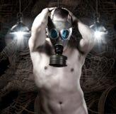 Uomo nudo con la maschera antigas su fondo dei robot e della tecnologia Fotografia Stock