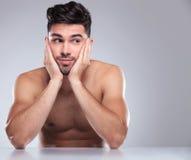 Uomo nudo con la testa in sue palme che guardano al lato fotografia stock