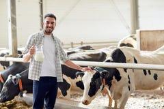 Uomo o agricoltore con il latte di mucche sull'azienda lattiera Immagini Stock Libere da Diritti