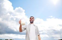 Uomo o agricoltore con la brocca di latte alla campagna Fotografia Stock