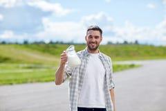 Uomo o agricoltore con la brocca di latte alla campagna Fotografie Stock
