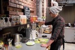 Uomo o barista che cucina frullato al caffè del vegano Fotografie Stock