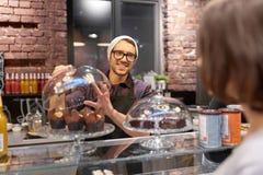 Uomo o barista con i dolci che serviscono cliente al caffè Fotografia Stock