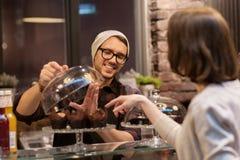Uomo o barista con i dolci che serviscono cliente al caffè Immagine Stock