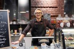 Uomo o barista felice del venditore al contatore del caffè Immagini Stock Libere da Diritti