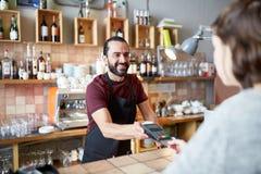 Uomo o cameriere con il lettore di schede ed il cliente alla barra Immagini Stock Libere da Diritti