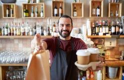 Uomo o cameriere con il sacco di carta e del caffè alla barra Fotografia Stock
