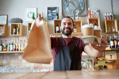 Uomo o cameriere con il sacco di carta e del caffè alla barra Fotografia Stock Libera da Diritti