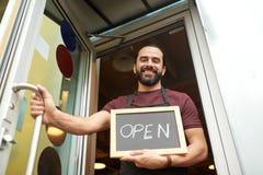 Uomo o cameriere con la lavagna alla porta di entrata della barra Immagini Stock
