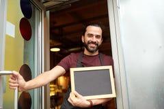 Uomo o cameriere con la lavagna alla porta di entrata della barra Fotografia Stock Libera da Diritti