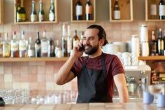 Uomo o cameriere felice alla barra che rivolge allo smartphone Fotografia Stock