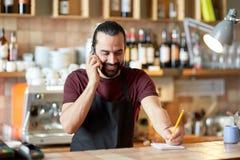 Uomo o cameriere felice alla barra che rivolge allo smartphone Immagini Stock