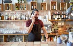 Uomo o cameriere felice alla barra che rivolge allo smartphone Fotografie Stock